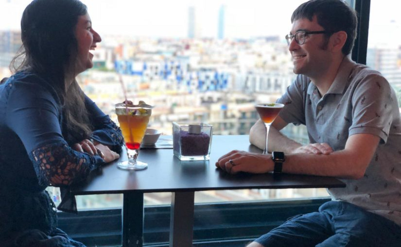 Josh and his wife in barcelona with cocktails and a city view
