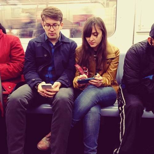 rob and mary looking at phones on the subway